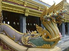 Naga emerging from the mouth of a Makara in the style of a Chinese dragon