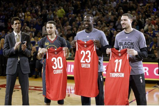 Golden State Warriors General Manager Bob Myers, left, applauds as the Warriors' Stephen Curry (30) Draymond Green (23) and Klay Thompson (11) display their All Star Game jerseys this week. All three are playing for the Western Conference team. 2/10/2016