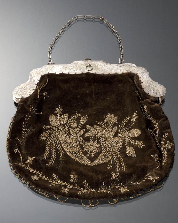 Beugeltas met gegraveerde beugel van tweede gehalte zilver en fluwelen tas met bloempatroon van zilverkleurige kraaltjes. De achterzijde van de tas is niet bewerkt. De beugeltas is gebruikt door een vrouw uit Blaricum (1865). Dit type tasbeugel werd gedragen in diverse streken van Nederland. #Blaricum #Gooi #NoordHolland