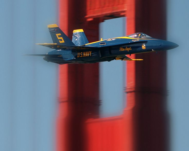 A US Navy Blue Angels F18 passes in front of the south tower of San Franciscos Golden Gate Bridge.