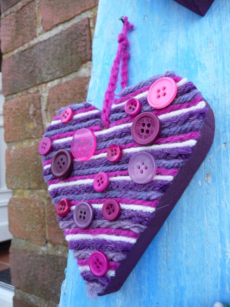 Hanging wood  and wool heart, with pink, purple & cream stripes and random buttons