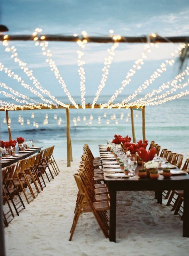 Keep it simple for your beach wedding reception with minimalist flower arrangements + fun string lighting.