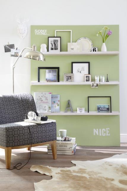 Weißes Bilderregal vor grüner Wand