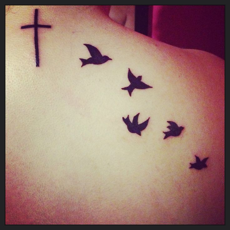 Cross and bird tattoo; symbolizes freedom from the restraint of societal expectations.