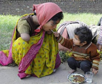 A young boy helps feed his mother, who has tragically lost both of her arms.