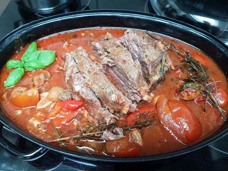 Een mooi stuk rundvlees van een kilo in gekruid met koriander peper en zout takjes rozemarijn basilicum tomaten en tomatenpuree spekjes lekker alles door elkaar mengen en 6 uurtjes in de over heerlijk!!