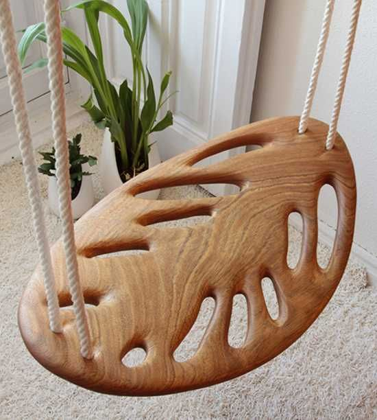 Charming wooden swings, designed by Veronica Martinez, bring beautiful shapes and green leaves patterns into modern homes, offering playful seating design for outdoor home decor. Inspired by the falli