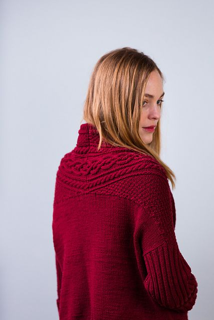 Lush cables and moss stitch make the most of Arbor's beautiful stitch definition in this striking, sculptural cardigan. A dramatic collar is formed by extending the fronts to wrap around the shoulders and join behind the neck. The back is picked up from the edges of the joined shoulders and knit downward as a square of stockinette with a ribbed hem. Double-ribbed sleeves are picked up and knit flat down to the cuff. Side seams are sewn to complete the piece. Knit in Vintner or another bright…