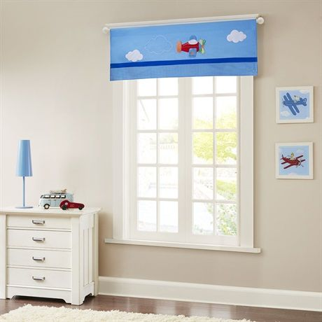 Take flight with our Totally Transit Window Valance, perfect for bringing a little fun to your child's room. Embroidery and applique detail come together to create cool clouds for a colorful airplane, while plush mink fabric help create soft texture and dimension for a unique update. Features solid blue ribbon and a printed gingham bottom border, that works perfectly with coordinating bed and dec pillows for a complete look.