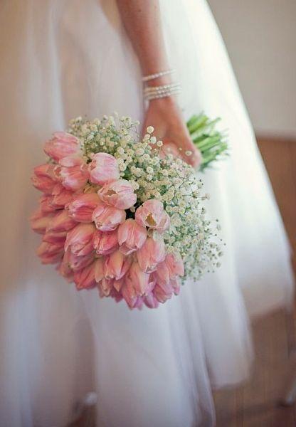 Supermooi bruidsboeket met roze tulpen met daaronder gipskruid.