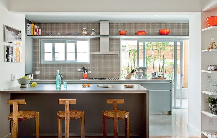 A cozinha do projeto da SAO Arquitetura é cinza, mas ganha graça com as panelas coloridas e as banquetas Girafa