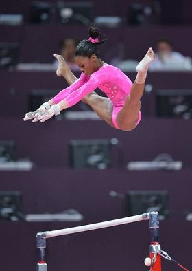 Gabby Douglas warms up her uneven parallel bars routine during Olympics podium training in London for USA Gymnastics' women's team.