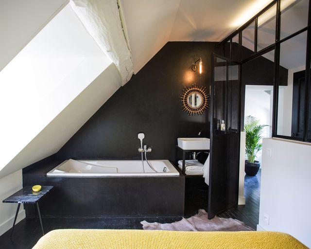 Sous les combles, une salle de bains noire avec une verrière.