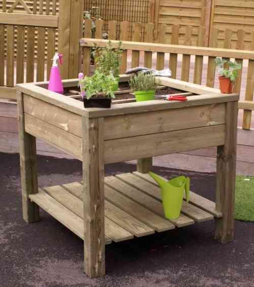 Potager en hauteur Une vue d'une table de culture sur pieds en bois