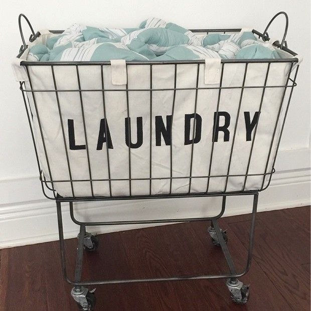 "Fabric Lined Metal Rolling Laundry Cart. Overall: 24.5"" x 16"" x 27"" H. $92.  May be too small for an actual laundry hamper, but could be used for other things."