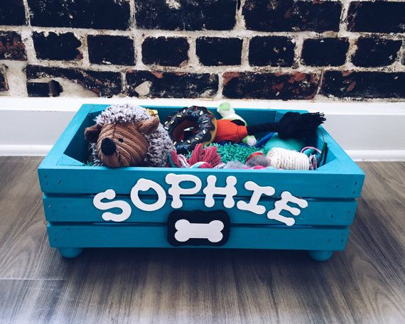 Keep all those ropes, balls, and chew toys in one handy place with this Rustic Dog Toy Box. This hand-crafted box is made from pine and given a hand-painted matte chalk bright blue finish for lasting durability. Each box is customized so that your dogs name appears with hand finished lettering.  The Toy box is approximately: 9.5 wide x 16 long and 6 high  IMPORTANT: Legs come separately and can be easily assembled with a little glue (wood or krazy glue)  When checking out please add a note…