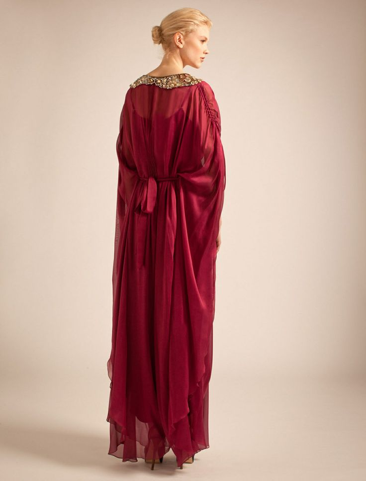 A Temperley Classic, the Oberon Kaftan is made using fine gloss chiffon that gathers at the waist with a hidden tie and falls in a delicate swathe of silk to the knee. Sleeves are dramatic and full, gathered with a channel up the arm which can be shortened or lengthened. The nipped in waist has a central panel encrusted with glittering mounted crystals, cleverly drawing the eye in to the narrowest point and mirrored on the shoulder with two sparkling epaulettes. The ultimate glamorous ...