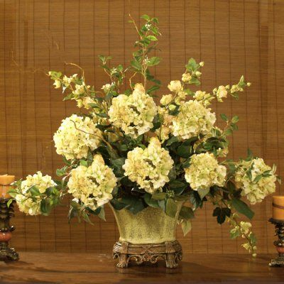 Green Hydrangeas in Scalloped Vase Silk Flower Arrangement AR22. Accent your home with this elegant silk floral design from our designer collection. The grande size will help fill a large dining table or a first impression as a foyer accent. Soft natural greens & cream hydrangea with foliage come together in a cream, green crackle scalloped resin vase.