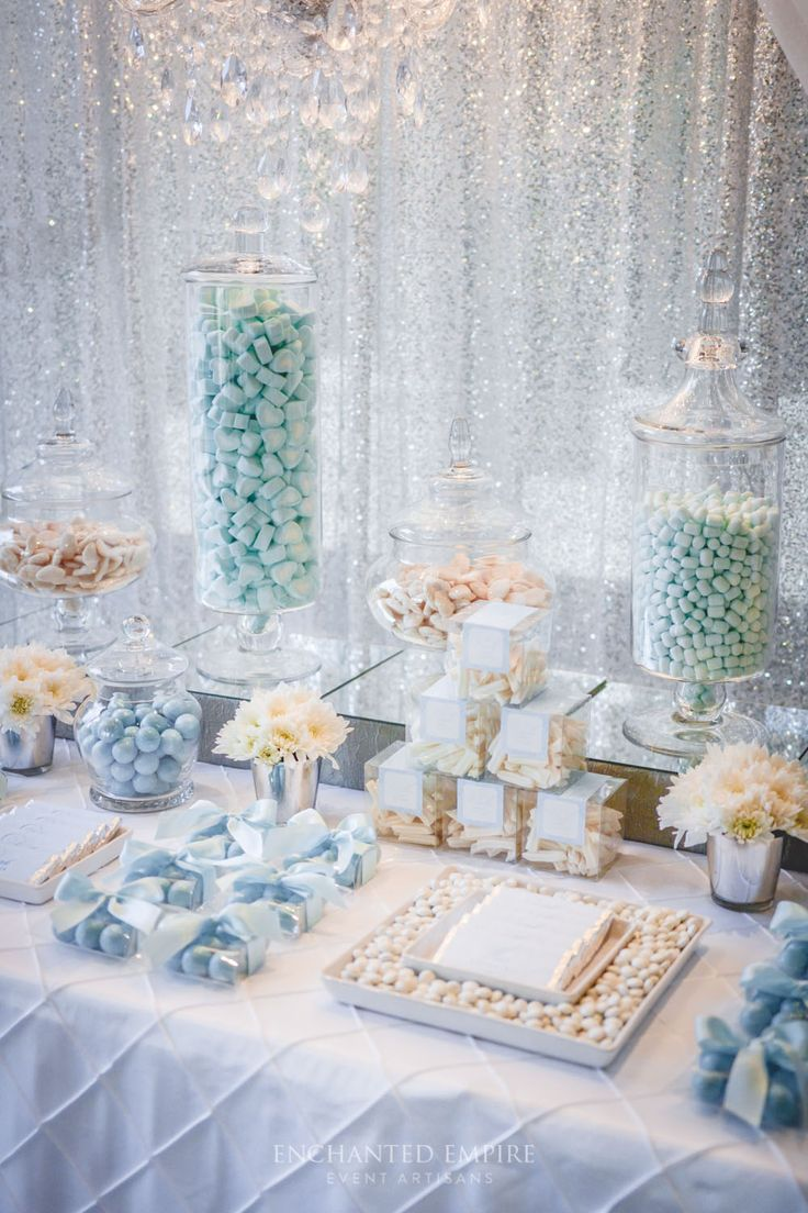 A glistening silver sequin backdrop framed this elegant sweets table perfectly. Complimented by cascading draping and a crystal drop chandelier to illuminate and accent the array of perfectly packaged sweets, custom designed chocolate bars, and colour matching candy. Extravagantly detailed, this lolly buffet was a truly memorable gift for guests to remember. Youtube: https://www.youtube.com/watch?v=mrhEmG37IWQ