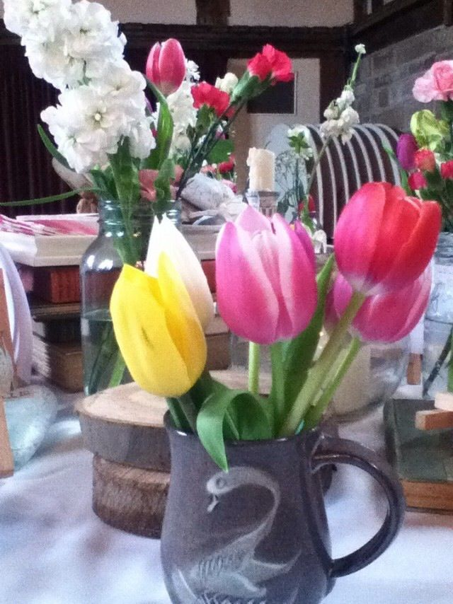 Tulips in a vintage tea cup, with slices of eucalyptus and old books behind