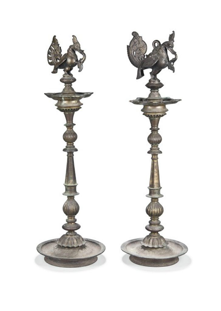TWO LARGE BRONZE CANDLESTICKS WITH MYTHICAL BIRDS  DECCAN, INDIA, 18TH/19TH CENTURY  Cast, each with tray base on short flared foot, the faceted and ribbed shaft supporting a five-spouted oil bowl, with perched mythical bird (hamsa) at top 32½in. (82.5cm.) high