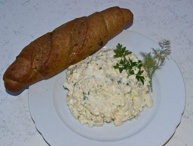 Für den Eieraufstrich die hartgekochten Eier schälen und klein hacken. Zwiebel, Schnittlauch, Dill, Petersilie und die Essiggurkerl ebenso fein