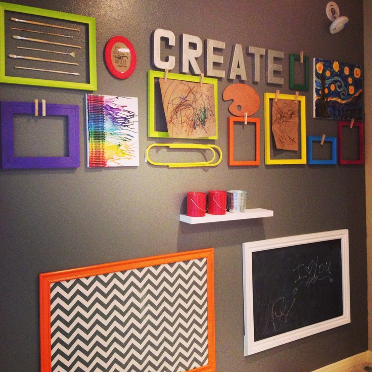 Art gallery wall using backless frames with clothespins hot glued on. Plus a homemade crayon art on canvas, giant paper clip from hobby lobby, magnetic board covered with fabric, and store-bought chalkboard.