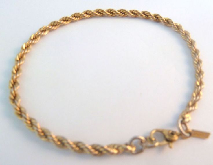 A vintage gold tone rope chain bracelet by Monet This dainty bracelet is formed from a twisted gold tone rope chain bracelet A Monet hang tag is set