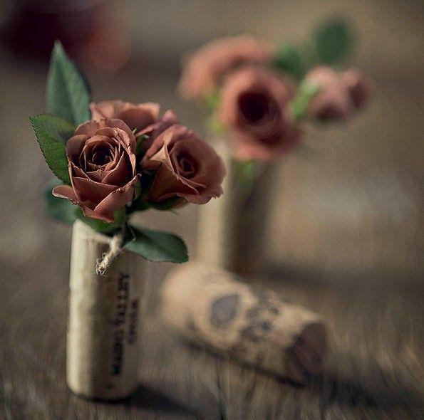 Rolhas com uma cavidade acomodam minirrosas (amarre algodão molhado no caule para que durem mais). Pequenos arranjos individuais de grande efeito na mesa