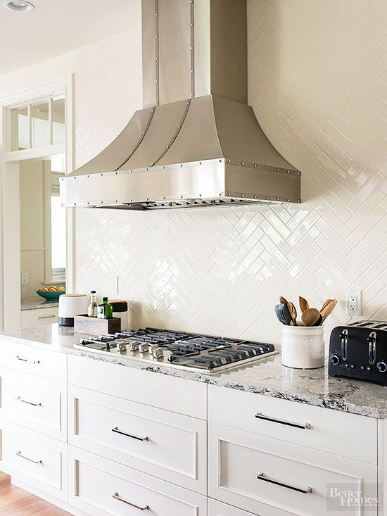 Glossy tiles -- basic subway tile in a herringbone pattern -- cover the entire wall behind the vent hood for a high-impact, low-maintenance backsplash.