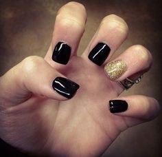 A sparkly gold ring finger nail with dark black nail polish. perfect acent in the snow