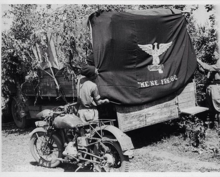 Ucraina, 1942. Camicie nere stendono una bandiera sul retro di un autocarro, col noto motto. Pin by Paolo Marzioli