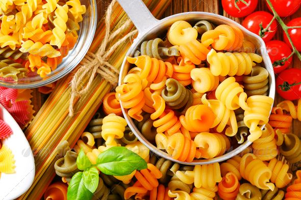 Various types of colored pasta ...  Bow Tie Pasta, Dried Pasta, Italian Cuisine, above, assortment, bowls, colored pasta, detail, farfalle, flavored pasta, food, green, ingredients, orange, overhead, pan, pasta, pasta colorata, pasta spirals, pasta twists, purple, raw, spaghetti, spirali, top view, trottole, uncooked, variety