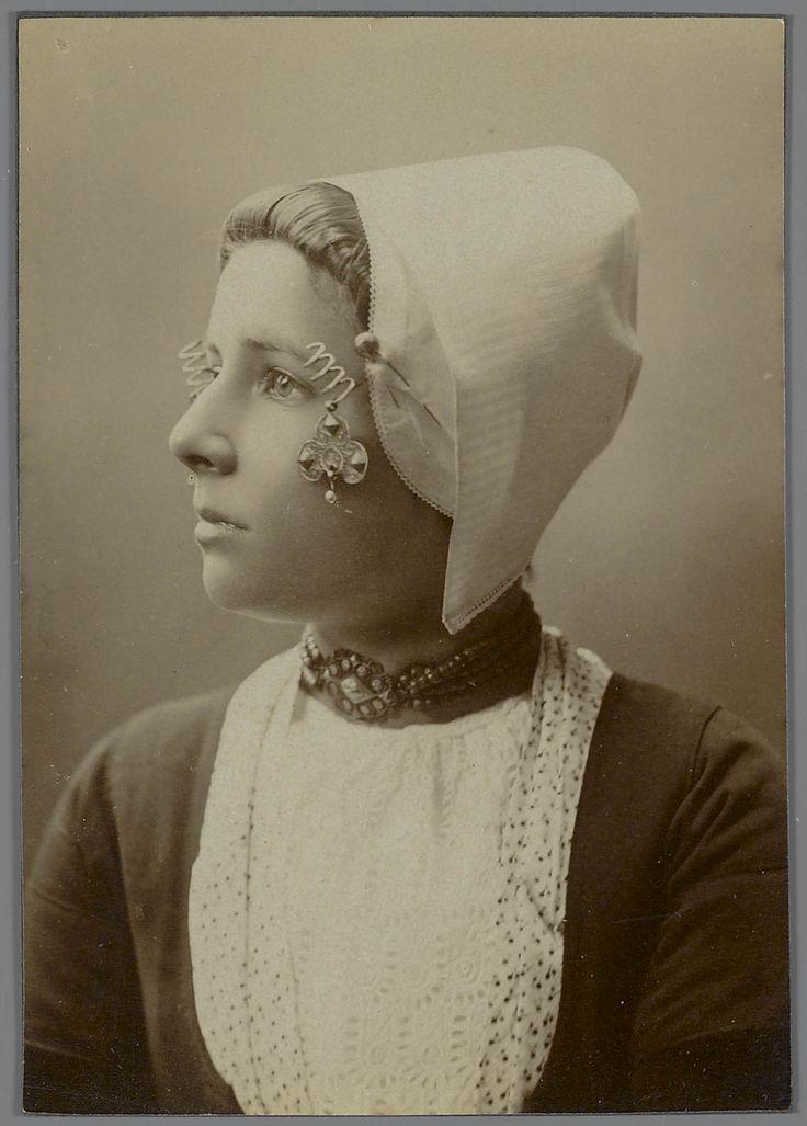 Jonge vrouw in Walcherse streekdracht ca 1880. Zondagse dracht. Onder de 'trekmuts' word een ondermuts gedragen, waarin het oorijzer is gespeld. Aan de uiteinden van het oorijzer bevinden zich gouden windingen, de 'krullen'. Aan de krullen hangen klaverbladvormige oorijzerhangers met een parel. Om haar hals draagt ze een halssnoer, met vier rijen kralen aan een ovale sluiting. In de uitsnijding van het jak zijn de schouderdoek en de beuk (kroplap) zichtbaar. #Zeeland #Walcheren