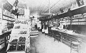 City Grocery in 1908, Queen and Walton street, with W.D. Stephens in front and Leo Greenaway behind the counter.