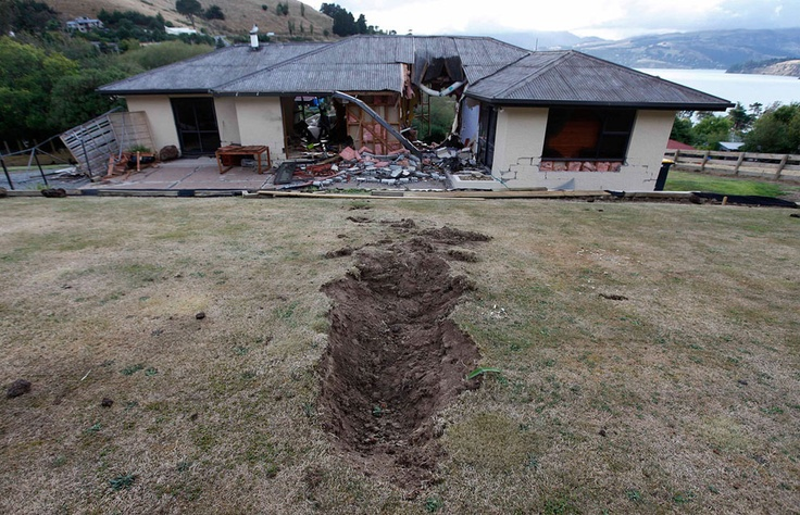 """""""Home Sweet Hole"""" A giant boulder punched a massive hole through this house during the February 22 earthquake near Lyttelton, a suburb of Christchurch, New Zealand. This photo was taken two days later. (AP Photo/Mark Baker)"""