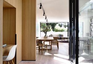 La scelta di creare delle pareti attrezzate in legno spezza l'ambiente giorno, accentuando il senso di calore dell'ambiente. Nell'angolo studio in primo piano si vede la sedia in plastica e legno degli Eames per Vitra, modello con scocca bianca