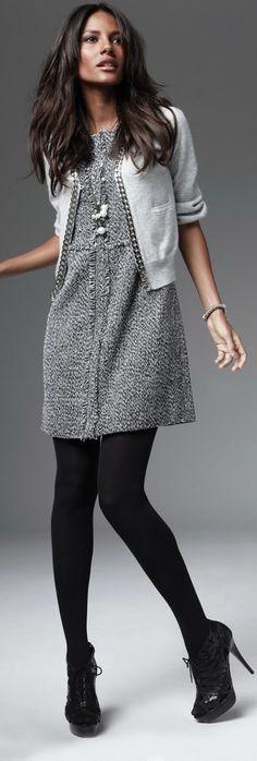 Vestido gris, medias y botines negros, chaqueta gris claro. Detalles en plata.