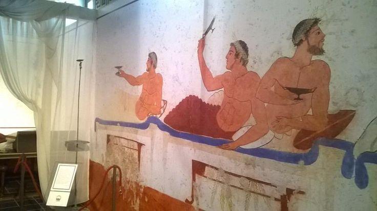 Scena di banchetto dalla Tomba del Tuffatore di Paestum (480 - 475 a.C): un banchettante gioca al Kottabos. Sulla sinistra in esposizione in anteprima nazionale il Kottabos di Vetulonia