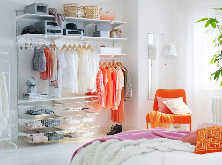 A light bedroom with open storage consisting of shelves, wire baskets and clothes rods, all in white.