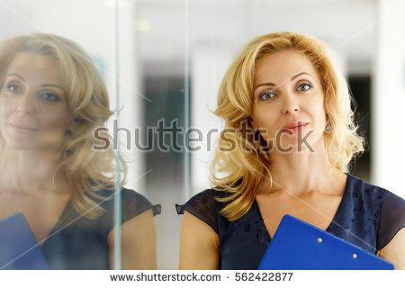 Mature blonde smiling businesswoman stand near glass door in office with blue clipboard pad in hands. Internal Revenue Service officer, white collar worker, certified public accountant concept