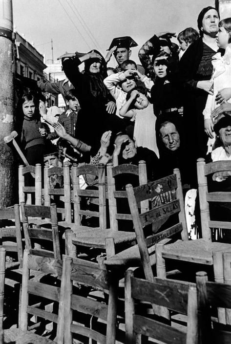 Seville, Spain. People watching a religious procession during the Holy Week. By Robert Capa, (April 1935)