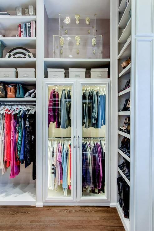 Walk-in closet boasts a built-in shoe shelves and clothes rails alongside a glass front wardrobe cabinet with custom lighting with overhead shelves filled with stacked lucite trunks accented with brass hardware.