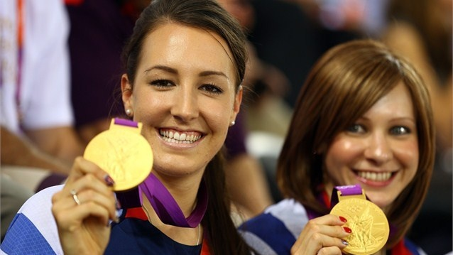 Dani King (L) and Joanna Rowsell of Great Britain pose with their medals as they visit to support team-mate Laura Trott of Great Britain compete in the Women's Omnium Track Cycling on Day 10.