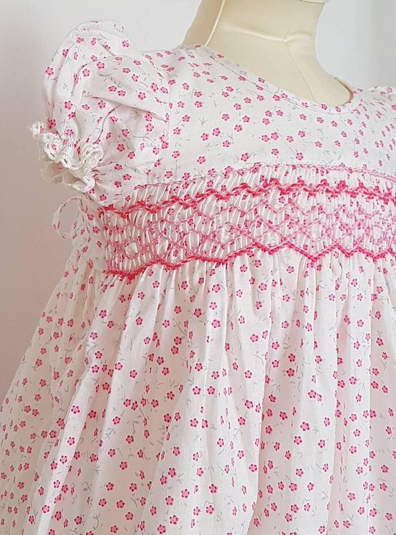 This gorgeous pink floral hand smocked baby dress has been made with a 100% cotton fabric with full cotton lining inside adorned with elegant hand smocking in two shades of pink. Sleeves and the hem of the skirt is edged with a fine baby cotton lace and the back closes with pink buttons and a tie back waist. Available in size - Size 6-9 months - Length of Dress from back of neckline to bottom of dress measures 18. Chest measurement is 20 around.