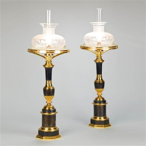 *A pair of Empire tole and lacquered brass Sinumbra lamps each having its original etched glass, partially frosted shade, supported in a resevoir with a brass border enriched with neoclassical ornament. The black marbled tole columns and octagonal plinths similarly mounted in lacquered brass. Now electrified - 1810.