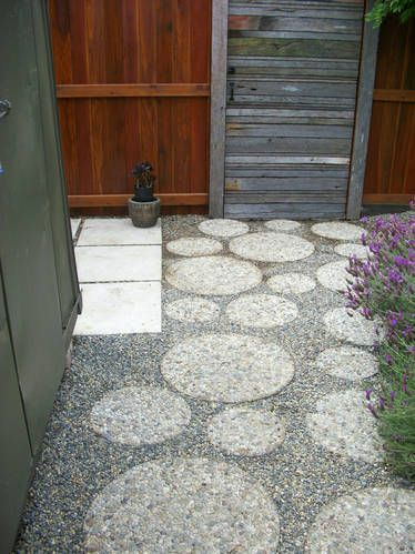 Round aggregate pavers in assorted sizes, set in a bed of pea gravel make a side yard more interesting.