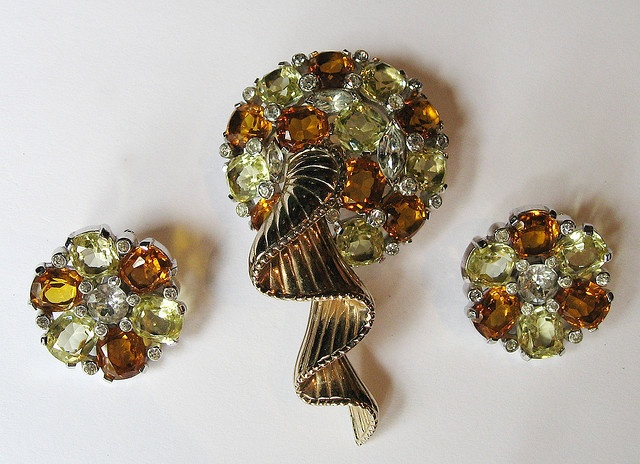 """Fabulous combination of square cut prong set citrine and amber coloured stones, accented with prong set clear marquise and paste set clear rounds stones. Stones are prong set in a rhodium plated setting. A 3-D gold toned ribbon flow from the centre of the pin. Jomaz is a division of Joseph Mazer of Mazer Brothers and was in production from 1946-1981. In excellent condition with minor gold loss to the back of the pin. Signed Jomaz. Circa 1950. Pin is 3"""" by 1 ½"""". Clip on Earrings are 1"""". #412"""