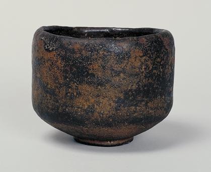 黒楽茶碗 銘「あやめ」 作者 長次郎 時代 桃山時代(16世紀後期) 黒楽茶碗 銘あやめ くろらくちゃわん めい あやめ 千利休の高弟南坊宗啓が著した『南方録』によると、天正15年(1587)五月中に利休は「茶碗 黒 渓蓀」を3回用いているが、本図の茶碗はそれにあたるものと推測されている。外箱蓋表に「あやめ 長次郎作 旦(花押)」、内箱蓋表に「長次郎焼 茶碗」と宗旦が書き付けている。同じく長次郎作の茶碗「まこも」の中箱に、久須美疎安が「あやめハ千宗守ニ有之」と記しているので、「あやめ」は、宗旦から一翁宗守、さらに官休庵に伝わったと思われる。後に永楽善五郎の所持となり、草間伊兵衛に譲られた。「大黒」や「俊寛」の形式とも違った独特の作行きの茶碗で、侘びの趣きの深い名碗の一つである。全体がかなり厚手に成形されており、胴にわずかにくびれがつけられていて、肌の起伏に言い難い趣きがある。高台は小振りで低く、高台内の兜巾は渦がなくおとなしい。畳付には目跡が5つ残っている。黒釉には長次郎焼特有の黄褐色のかせがむらむらと現れていて、いかにも古色蒼然とした趣きである。見込みはい...