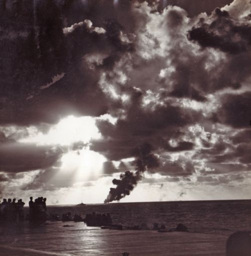 """""""Photograph taken from the carrier Yorktown (CV-10) showing a Japanese G4M """"Betty"""" bomber burning, 22 February 1944. Image is part of a scrapbook assembled by Lieutenant Commander Francis N. Gilreath during World War II documenting his service at Naval Air Station (NAS) Corpus Christi, Texas, and as flag secretary to Rear Admiral Alfred M. Montgomery."""""""